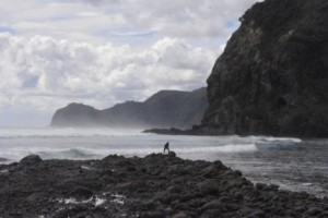 Late surfer at Piha with Lion Rock
