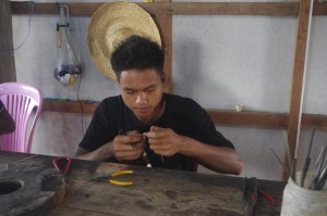 Boy making fish earings