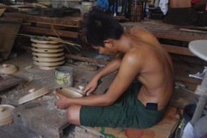 Lacquor Works. Youth with mobile phone tucked into his longyi